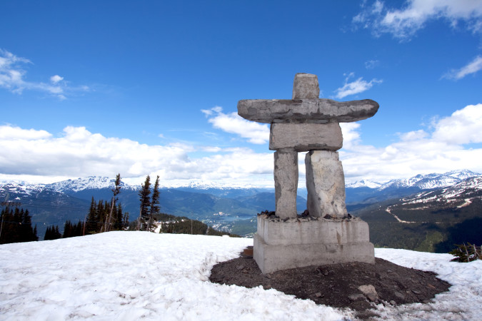 Whistler Peak inukshuk with snow and mountains